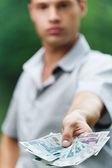 Portrait de jeune homme sérieux, donner de l'argent — Photo