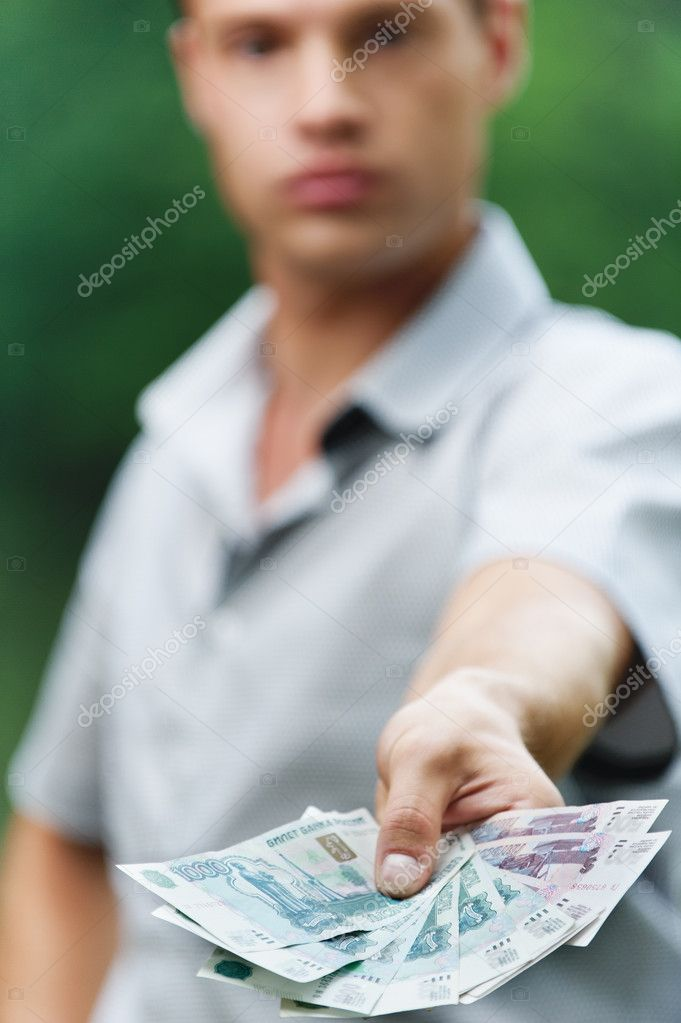 Portrait of young handsome serious man giving money at summer green park. — Stock Photo #6279670