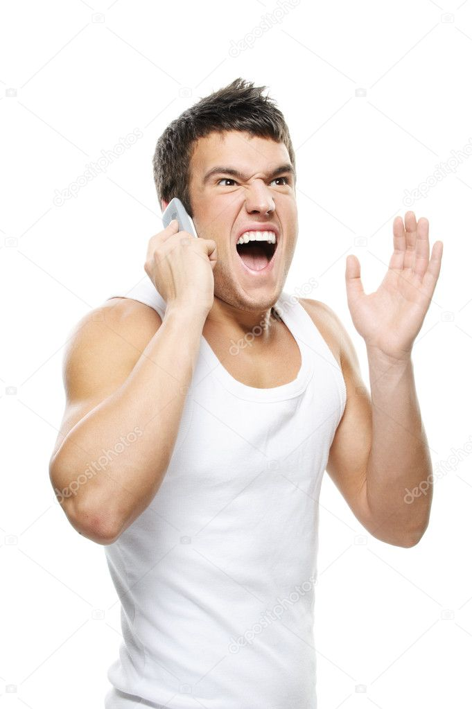 Portrait of young man wearing t-shirt, speaking on mobile phone and shouting against white background. — Stock Photo #6305884