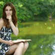 Portrait of young woman holding book - Foto Stock