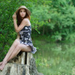 Portrait of young woman sitting on stump - Stock Photo