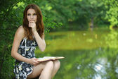 Portrait of young woman holding book — Stock Photo