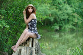 Portrait of young woman sitting on stump — Стоковое фото