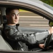 Portrait of handsome young man driving car - Stock Photo