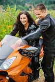Young couple with motorbike — Stock Photo
