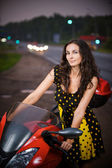 Portrait of young woman wearing dress standing near motorbike — Stock Photo