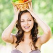 Portrait of young brunette woman holding basket full of fruits o — Stock Photo
