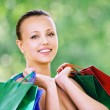 Portrait of smiling woman holding bags - Stock Photo