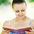 Portrait of young woman reading book — Stock Photo