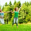 Two young women jumping - Stok fotoğraf