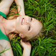 Portrait of young pretty woman lying on grass — Stock Photo #6527796