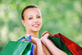 Portrait of smiling woman holding bags — Stock Photo