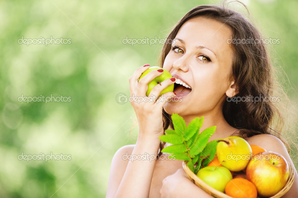 Portrait of young attractive dark-haired smiling woman holding basket full of fruits and eating apple at summer green park. — Stock Photo #6527752