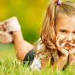Portrait of adorable little girl lying on grass — Stock Photo #6536975