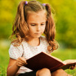Portrait of little cute girl reading book — Stock Photo