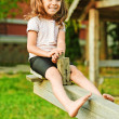 Little smiling girl on seesaw — Stock Photo