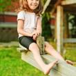 Little smiling girl on seesaw — Stock Photo