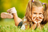 Portrait of adorable little girl lying on grass — Stock Photo