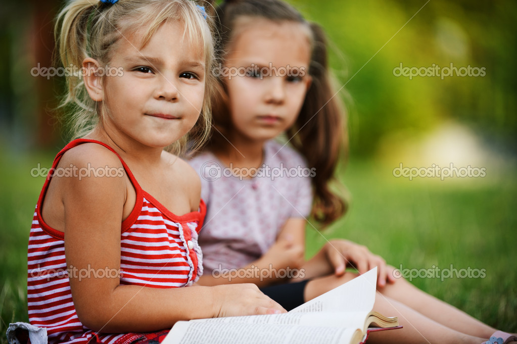 Two little pretty girls reading book at summer green park. — Stock Photo #6536976
