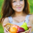 Pretty woman holding basket full of fruits — Stock Photo #6554579