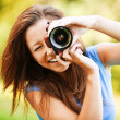 Young smiling girl making photo — Stockfoto