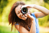 Young smiling girl making photo — Stock Photo