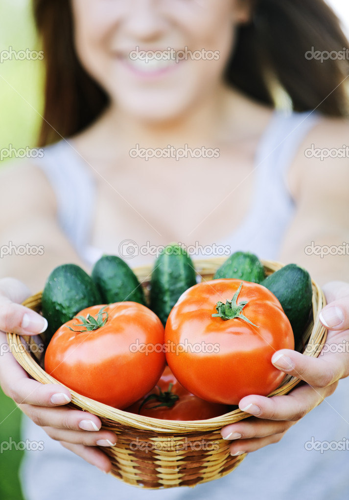 Young smiling woman holding basket full of ripe vegetables at summer green park. — Stock Photo #6554578