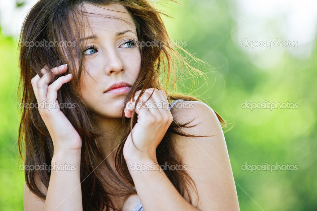 Portrait of troubled beautiful brunette girl looking somewhere at summer green park. — Stock Photo #6554588