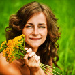 Portrait of beautiful woman holding bouqet of yellow flowers - Stock Photo