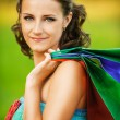Portrait of young smiling woman holding many bags — Stockfoto