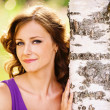 Stock Photo: Cute dark-haired womnear birch tree