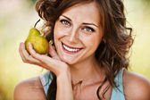 Portrait of woman holding pear — Stock Photo