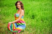 年轻漂亮的女人坐在草地上 — 图库照片