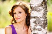 Cute dark-haired woman near birch tree — Stock Photo
