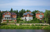 Houses on river bank — Stock Photo