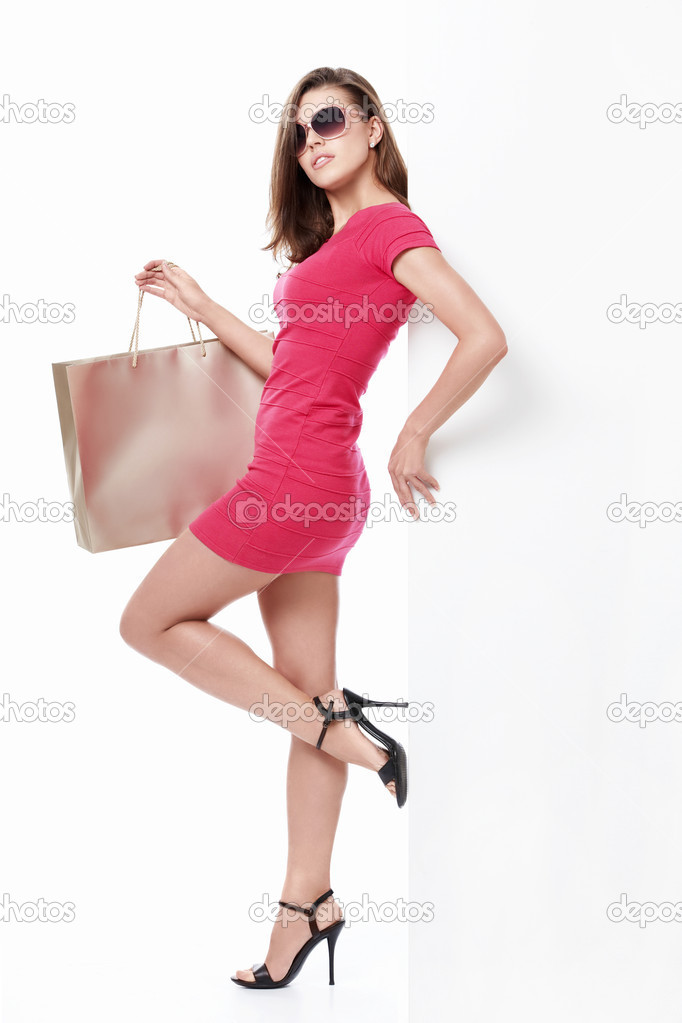 Sexy girl with shopping bags and empty the board on a white background — Stock Photo #5751971