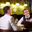 The waiter shows men in a pub menu — Stock Photo