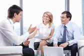 Two listen to a young man in the office — Stock Photo
