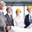 Business in hard hats looking up at the site — Stock Photo