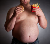 Fat man with hamburger and chips — Stock Photo