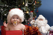 Cute Baby in red hat in front of Christmas Tree — Stock Photo