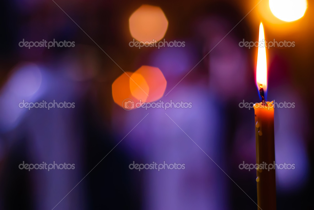 Burning candle on a blurred color background — Stock Photo #5535798