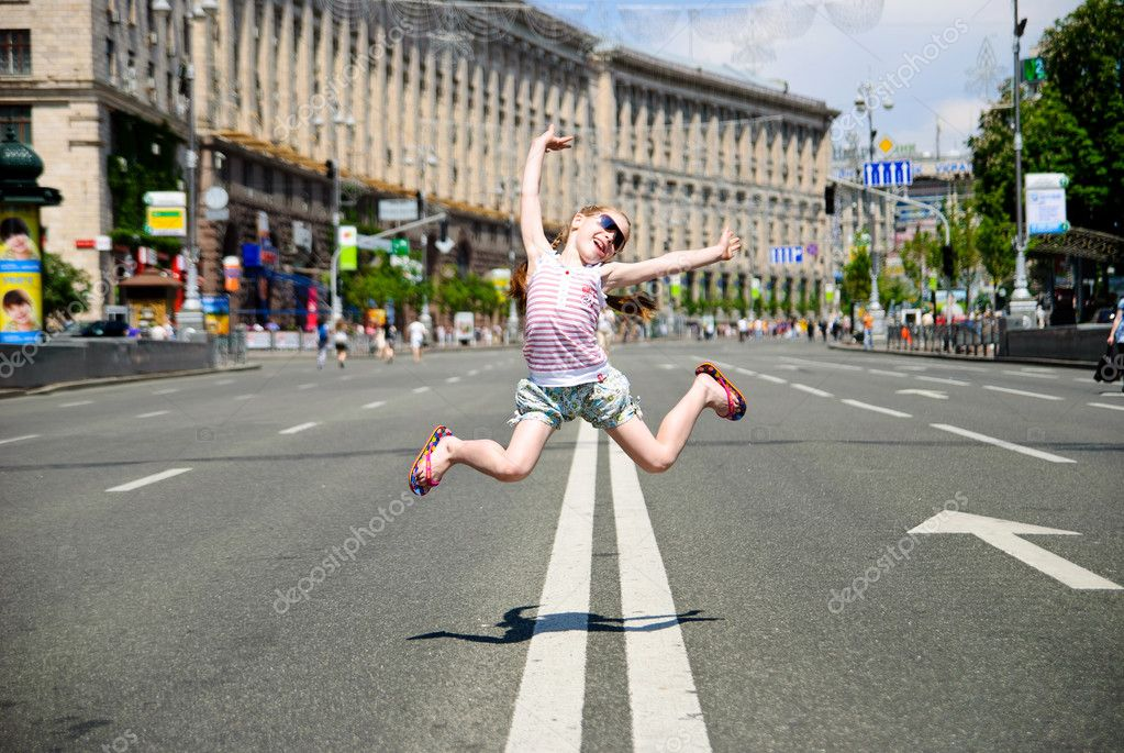 Little girl jumping in the middle of the street  Stock Photo #6529879