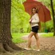 Young girl with an umbrella in park — Stock Photo