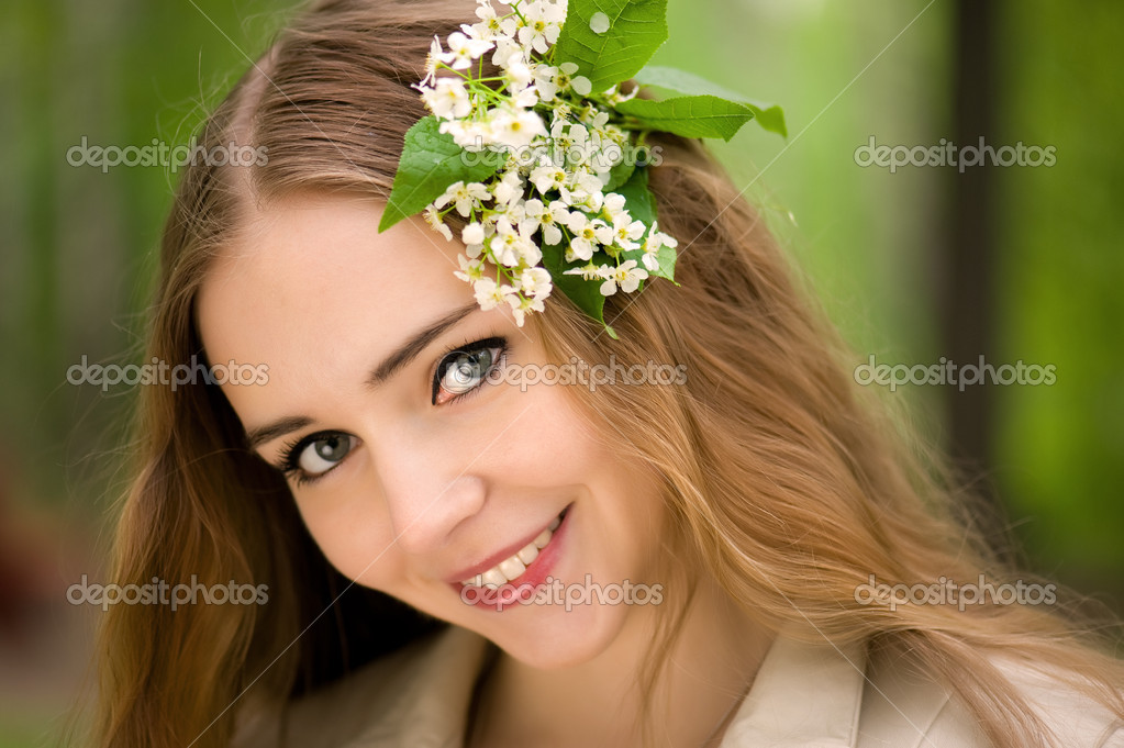Young girl with flowers in her hair in a summer park — Stock Photo #5805821