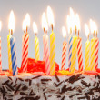 A birthday cake with lighted candles - Stock Photo
