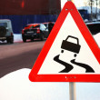 Varning sign for slippery road ahead — Stock Photo