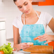 Attractive smiling woman preparing fresh healthy sandwiches in h — Stock Photo