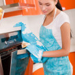 Beautiful young woman checking how her cake is doing in the oven — Stock Photo #5604174