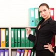 Business woman in front of shelves with folders — Stock Photo #5762028